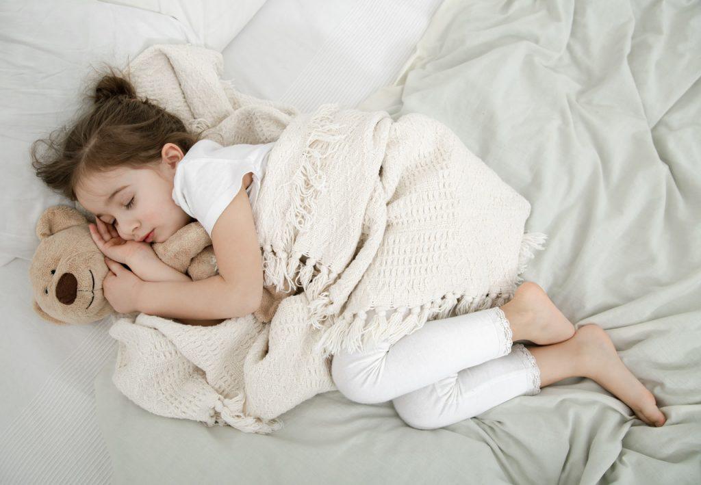 dziewczynka śpiąca na łóżku rodziców